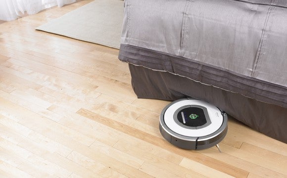 A robotic vacuum cleaning a wooden floor next to a bed.