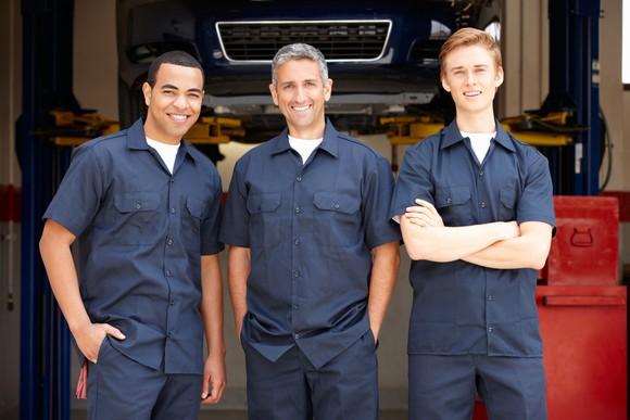 Three auto mechanics in matching work uniforms.
