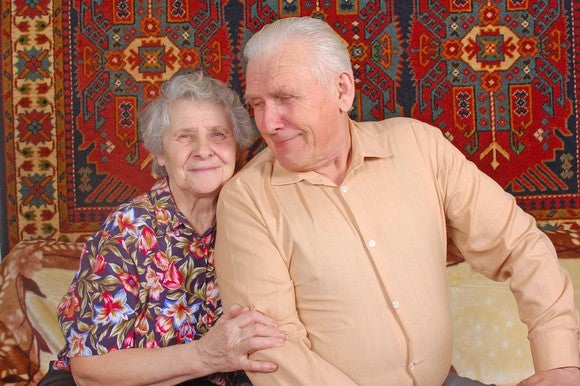 Elderly man and woman sitting on a couch.