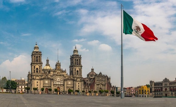 Mexican flag flying over a square with a large palacial building in background.