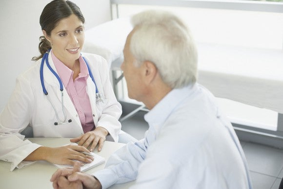 Young female doctor talking to older male patient