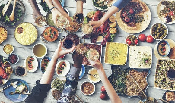 A table set with various foods. People off screen have their hands over the table toasting.