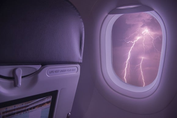 Airplane window looking out over dark clouds and thunderbolts.