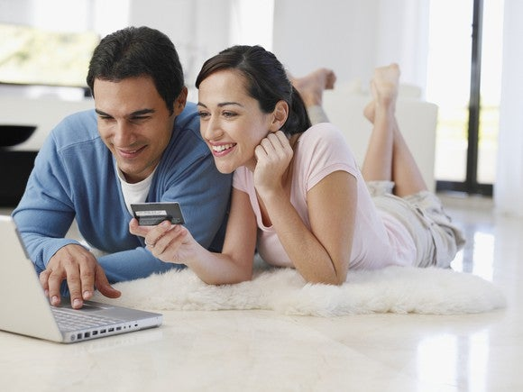 Couple lying on the floor at home entering credit card information using a laptop.