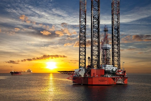 An offshore drilling rig with the sun setting in the background.
