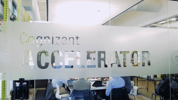 Glass wall with Cognizant Accelerator in glazed lettering, with partial view of offices beyond.