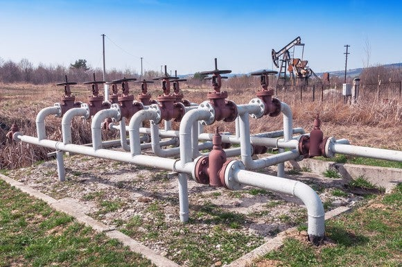 Natural gas pipelines and valves with an oil pump in the background.