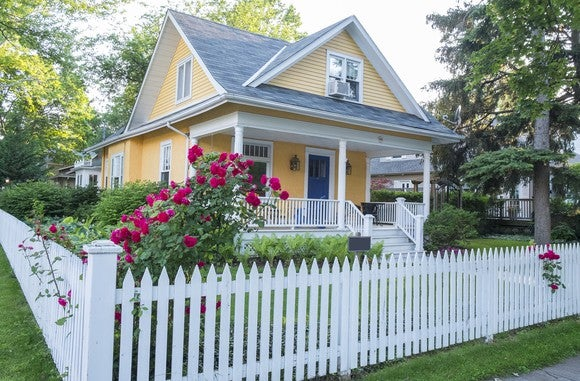 Yellow house with white fence around it