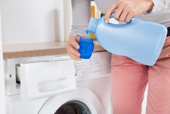 A person measures laundry detergent.