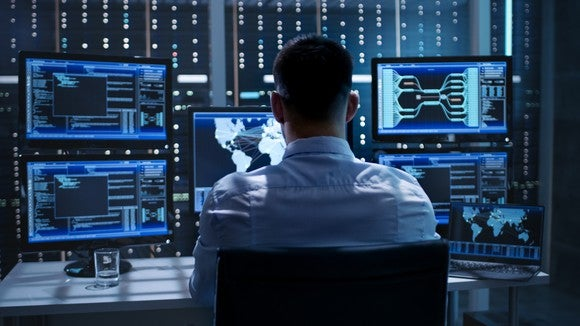 A person sitting in front of multiple computer screens