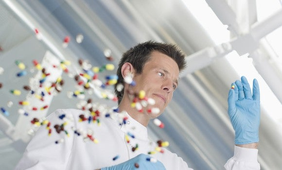 Man wearing white coat and blue gloves loooking at a pill, with dozens of other pills scattered on a glass table.