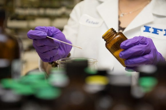 Person in lab coat and purple gloves swabbing contents of a brown bottle into a beaker.