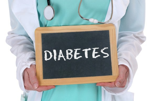 """A person in a lab coat holding a sign with the word """"diabetes"""" written on it."""