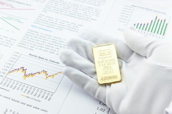 A hand with a white glove holding a gold ingot above a prospectus.