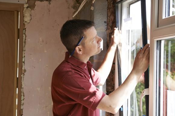 A contractor installs a window.
