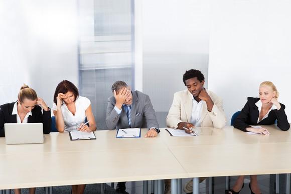 Business people looking upset in meeting.