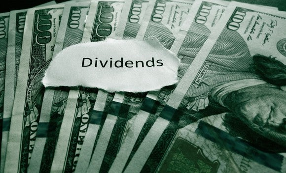 """Paper cut out that reads """"dividends"""" on top of $100 bills."""