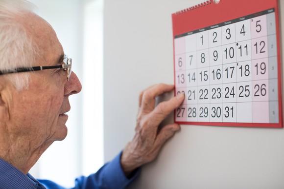 Senior man looking at a wall calendar