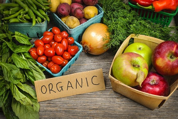 "Assorted fruit and vegetable on a table with a label that says ""organic."""