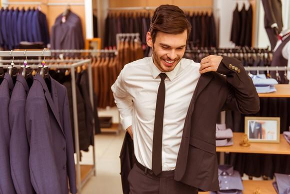 A man trying on a suit inside a suit shop