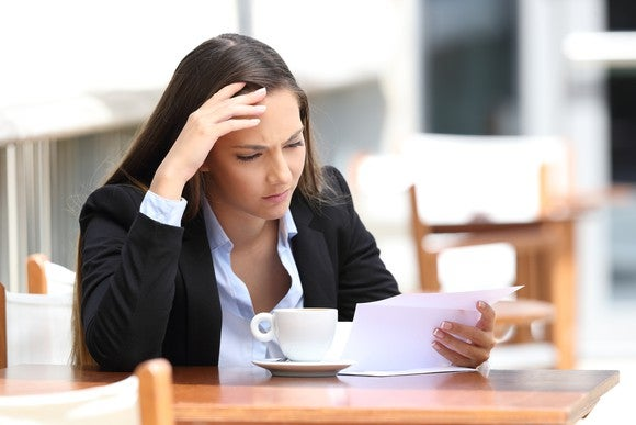 Woman with hand to forehead holds a piece of paper and sits at table with coffee cup on it