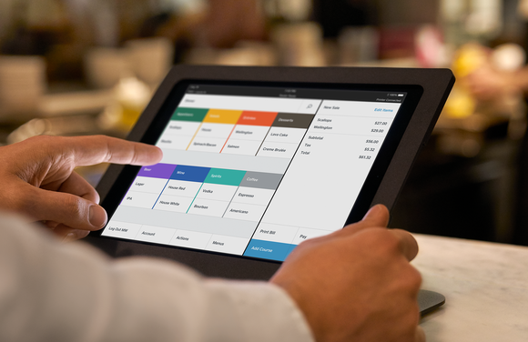 A person using Square for Restaurants on a tablet.