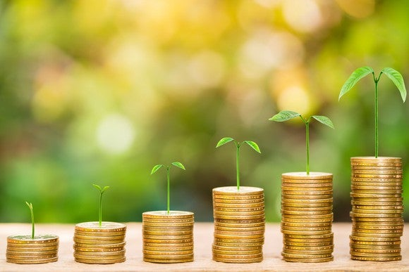 Stacks of coins growing successively taller with seedlings sprouting out of each stack.