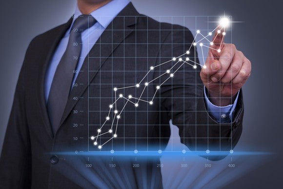 Man in a business suit pointing to an upward trending graph with his index finger.