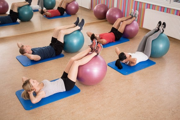 An indoor fitness class showing two young men and two young women each laying on a floor mat with legs raised on a ball.