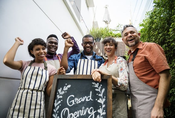 A group of people in aprons stand in front of a grand opening sign.