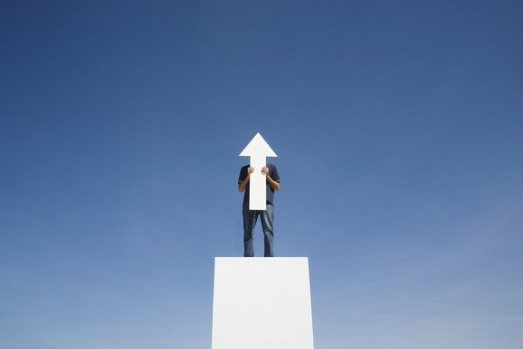 A man standing on a white column against a blue sky and he's holding a large white arrow cutout pointing up.