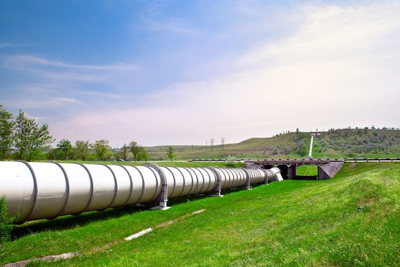 A pipeline on green grass stretching over the horizon.