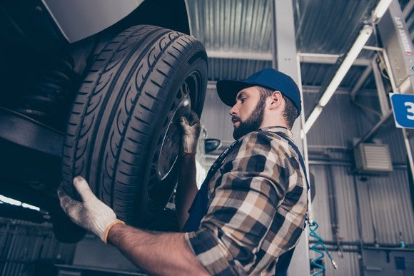 A man in a plaid shirt and a blue hat installing a tire in a garage.