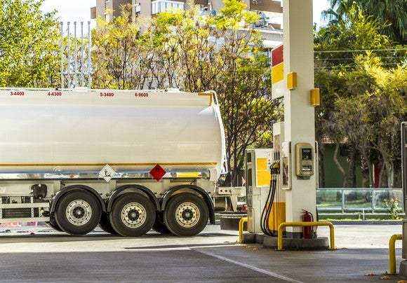 Natural gas tanker parked next to a fuel pump.