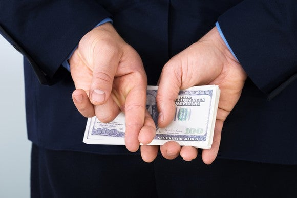 A businessman holding a stack of cash behind his back, with his fingers crossed.