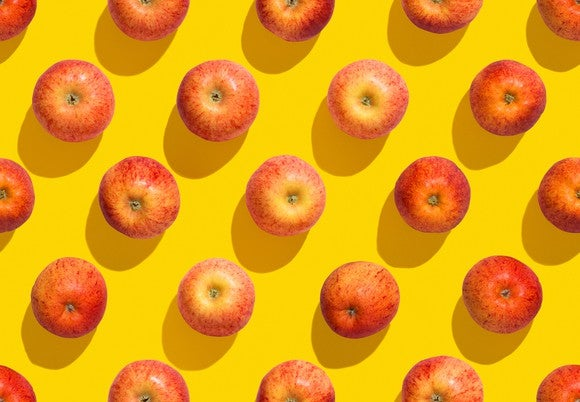 Evenly spaced apples on a yellow background