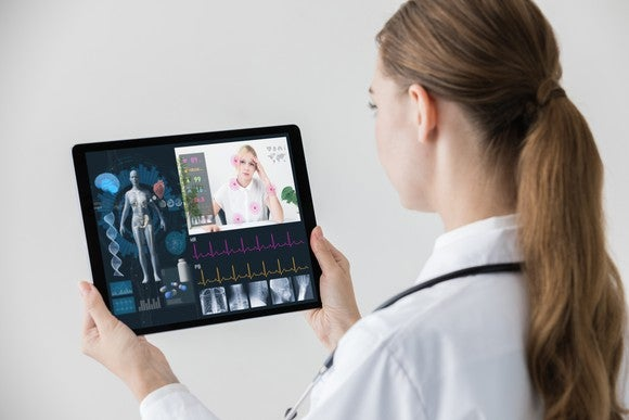 A female doctor holding a tablet and having a virtual consultation with a female patient