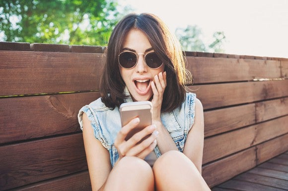 a young woman in sunglasses makes a surprised expression at her smartphone.