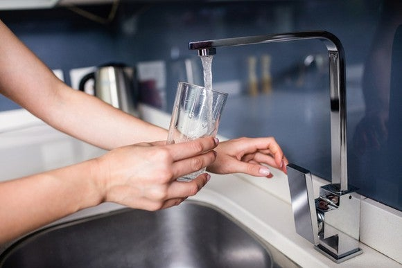 Person filling a glass under a water faucet.
