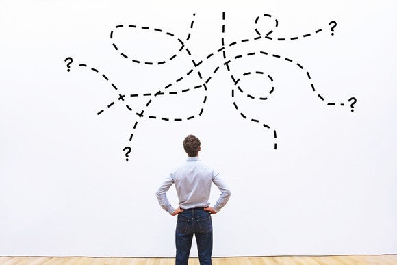 A man staring at a drawing of entangled dotted lines leading to question marks.