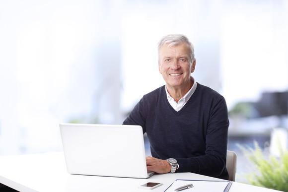 Older man sitting at a laptop, smiling