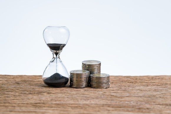 An hourglass sitting on a table next to three stacks of coins.