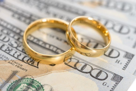 two gold rings sitting on some hundred dollar bills