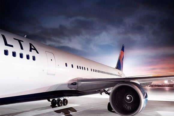 Delta aircraft as seen from left side, on a cloudy night near dusk on a white tarmac.