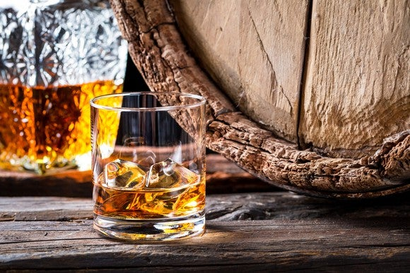 A glass of whiskey sitting next to a wooden barrel.