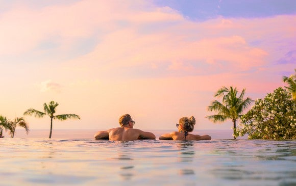 Two people leaning on edge of infinity pool with palm trees in the background