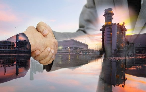 Two people shaking hands superimposed on an energy facility in the background.