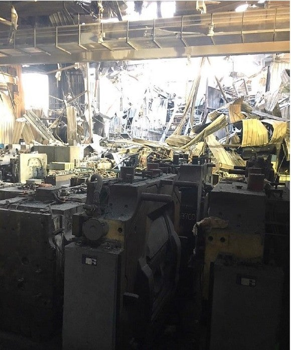 A photo of the factory floor after the fire, showing debris, tooling, and smoke damaged-walls.