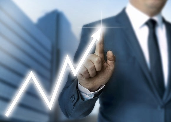 Man wearing suit pointing to line chart indicating sharp gains