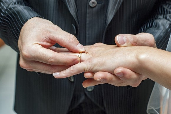 A man puts a wedding ring on a woman's finger.